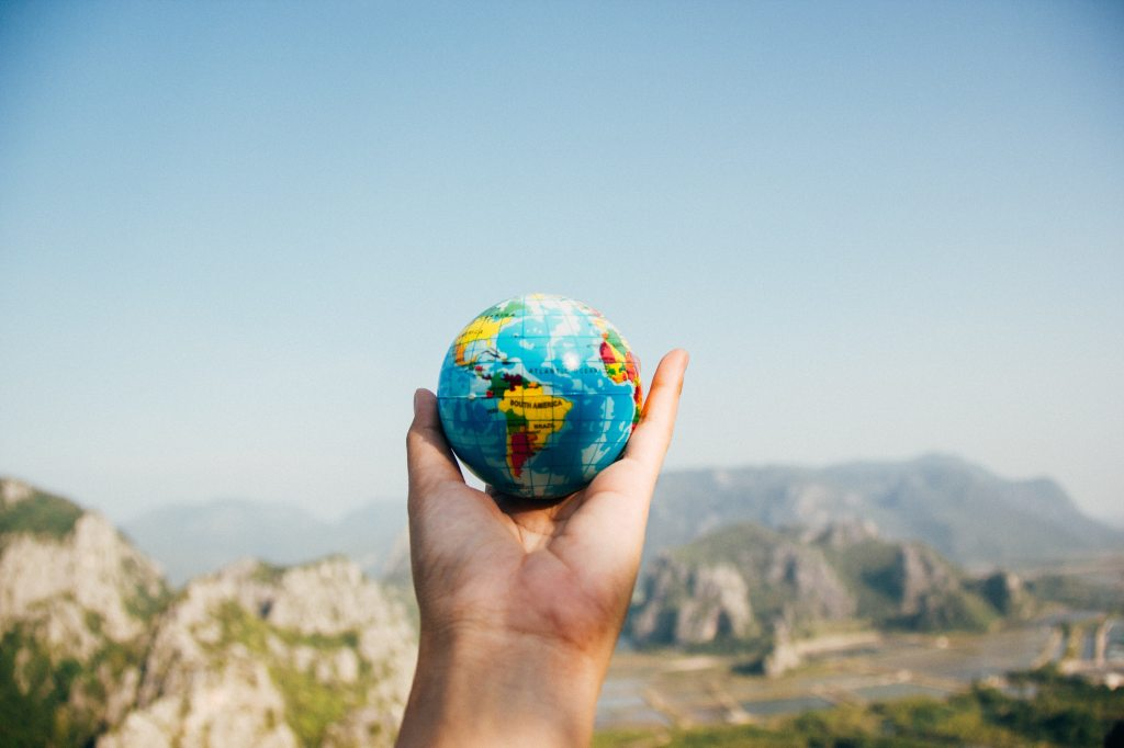 Small earth globe sitting in a persons hand with mountain scenery in the background.