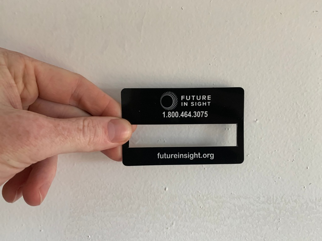 Black Signature Guide held in one hand. Future in Sight organization logo and information printed in white.