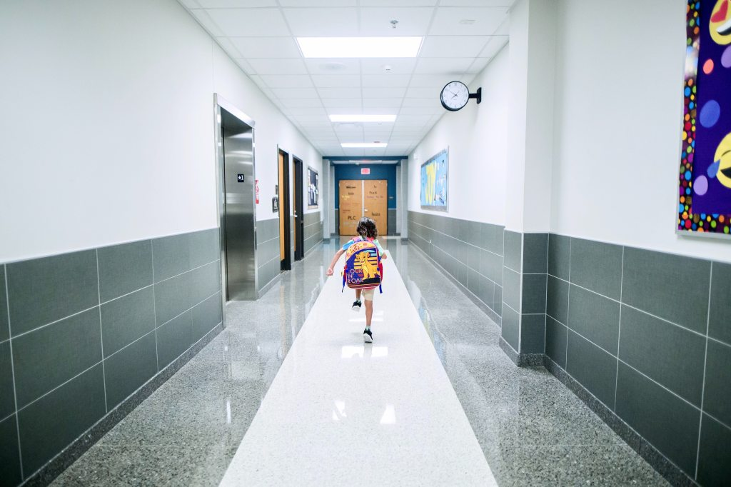 Boy wearing a backpack running down a school hallway with an elevator on his left