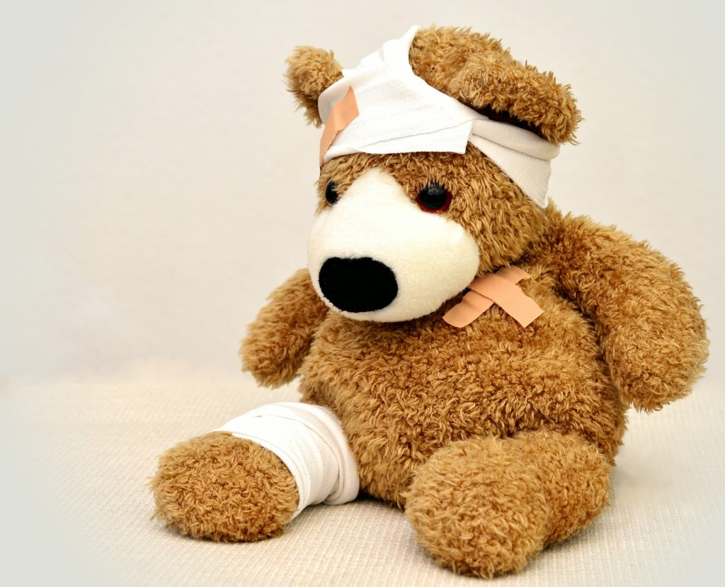 brown teddy bear covered in bandages. one on the head bandaids on the heart and bandage on right leg