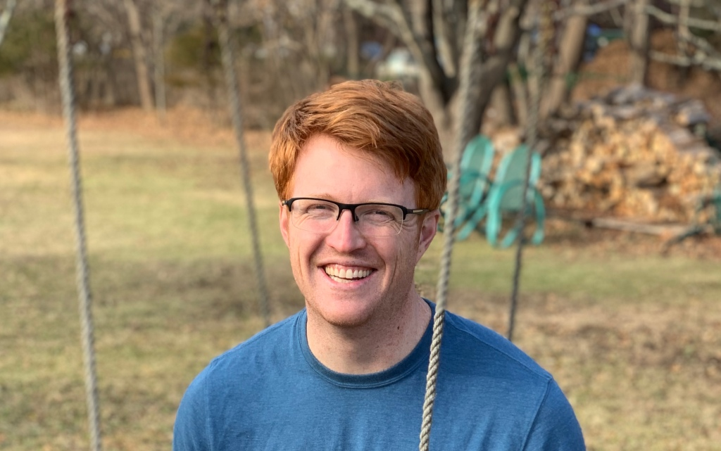 Man with red hair and glasses sitting on a swing and smiling