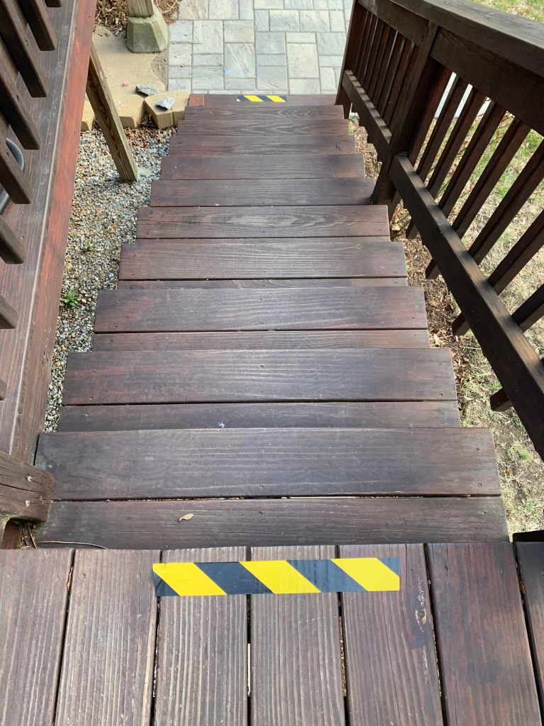 black and yellow striped tape on top and bottom step of brown wood staircase