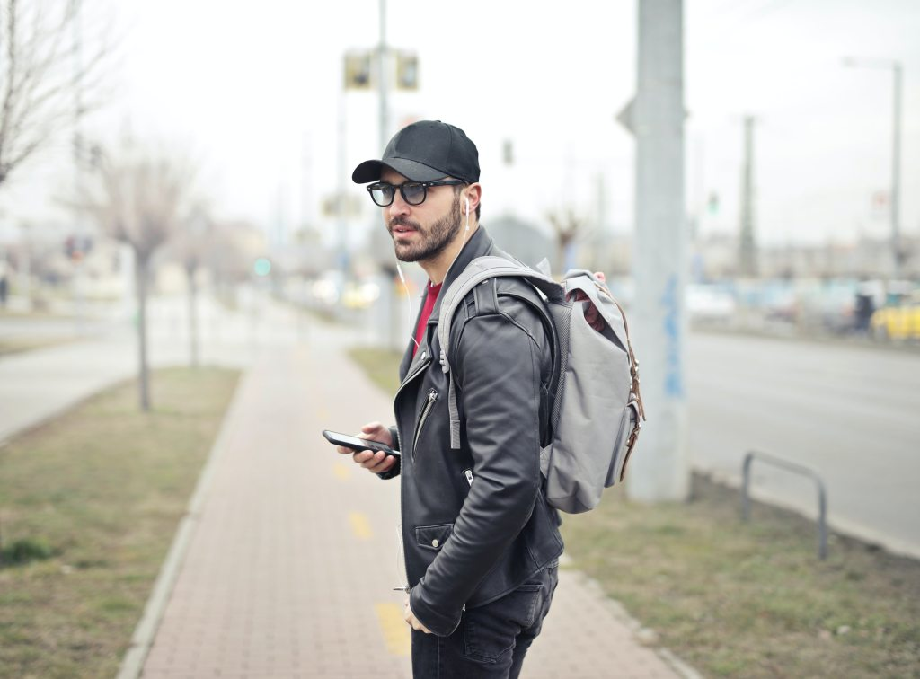 man wearing a black brimmed baseball cap wearing a grey backpack and holding a phone with headphones in his ears