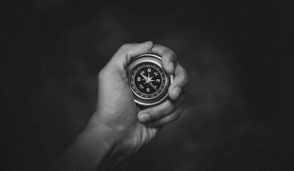 hand holding a traditional compass with a black background