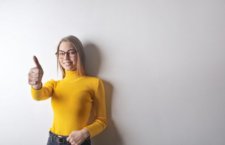 woman wearing a yellow turtle neck giving a thumbs up.