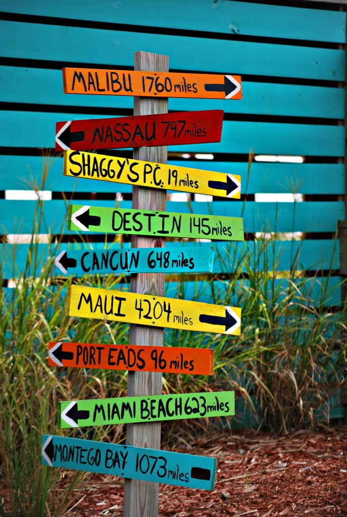 Signs with arrow directions pointing different ways to different towns.