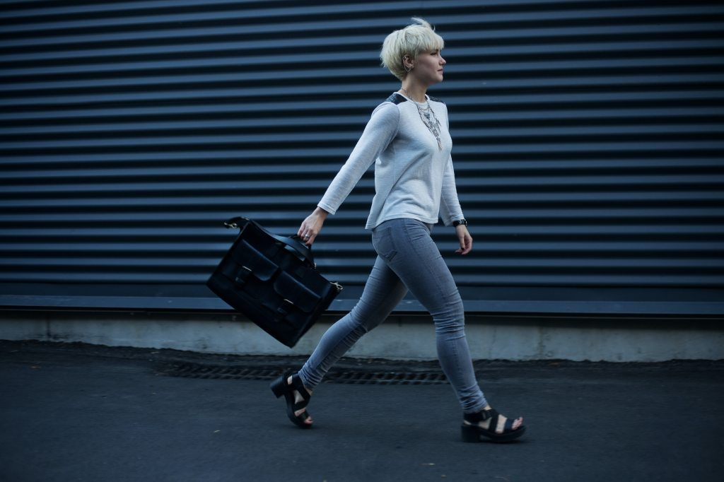 Woman wearing blue jeans with grey sweater, walking while carrying black handbag.