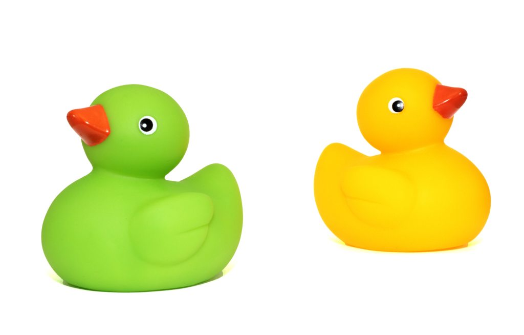 one yellow and one green rubber duck side by side