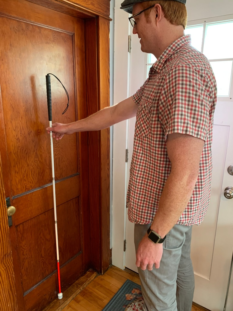 man holding a white cane vertically arms length away from a brown door