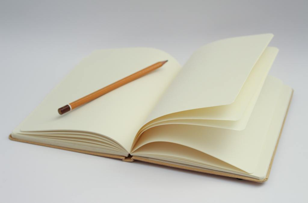 white notebook with yellow pencil