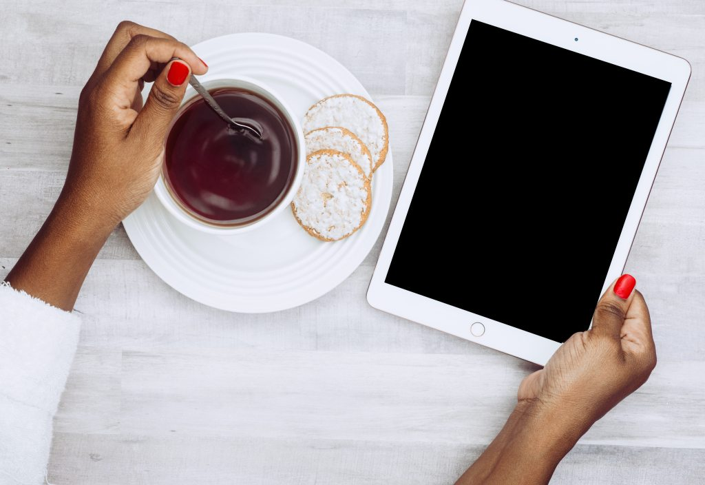 Person holding an iPad and stirringa cup of coffee