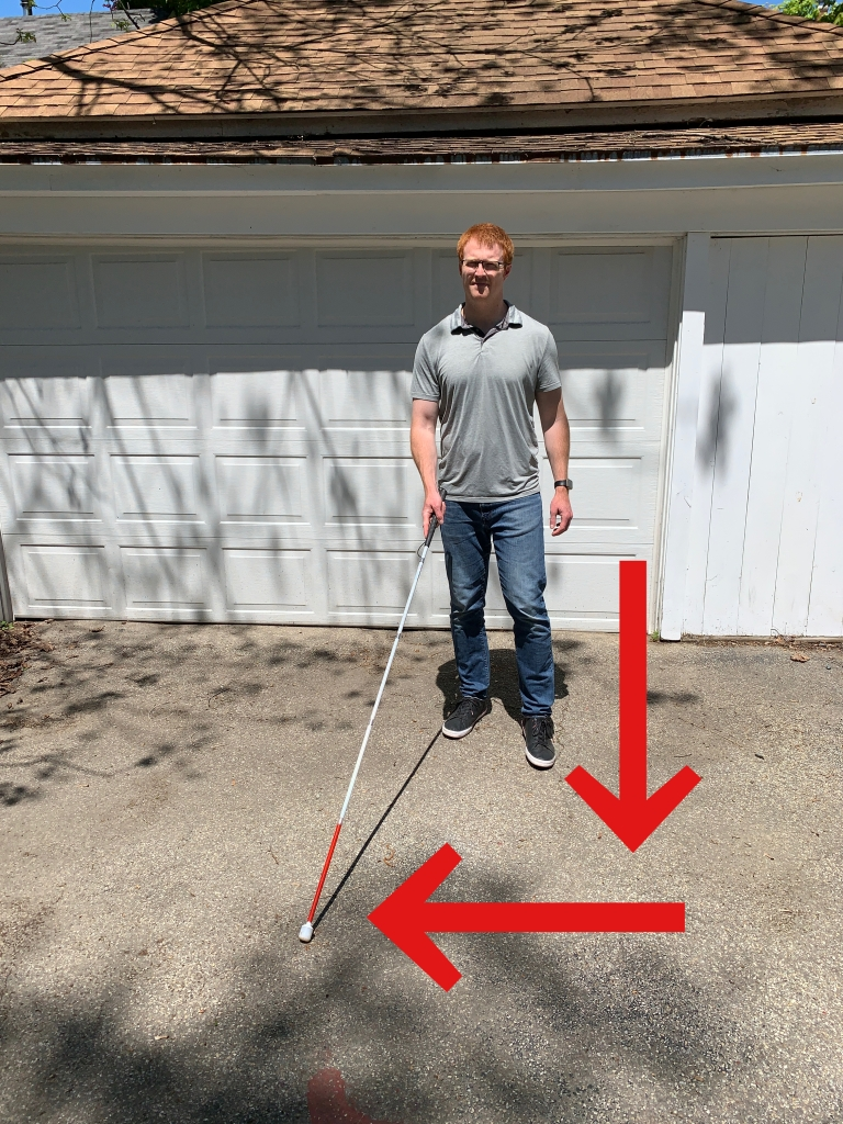 man in front of a white garage stepping forward  with one foot and sweeping a white cane at the same time