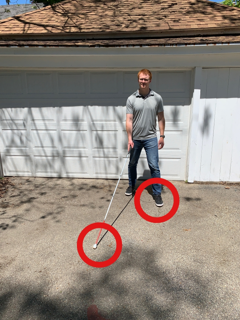 man in front of a white garage completing a step forward with one foot and cane tip on the ground on the opposite side. red circle around left foot and red circle around cane tip on the right side