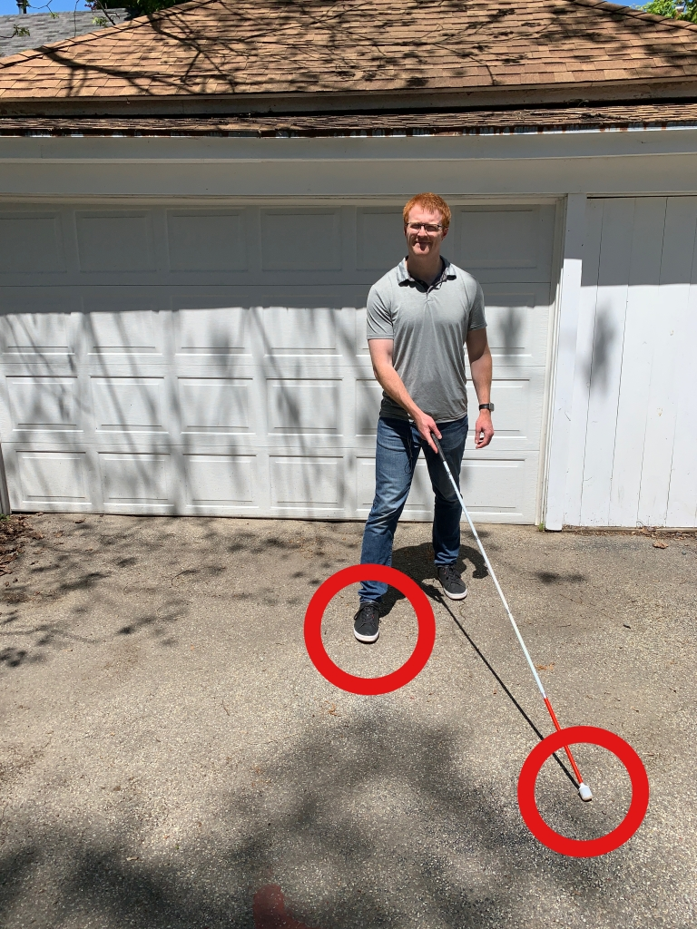 Man in front of a white garage taking a step with a red circle around the right foot and another red circle around the cane tip.
