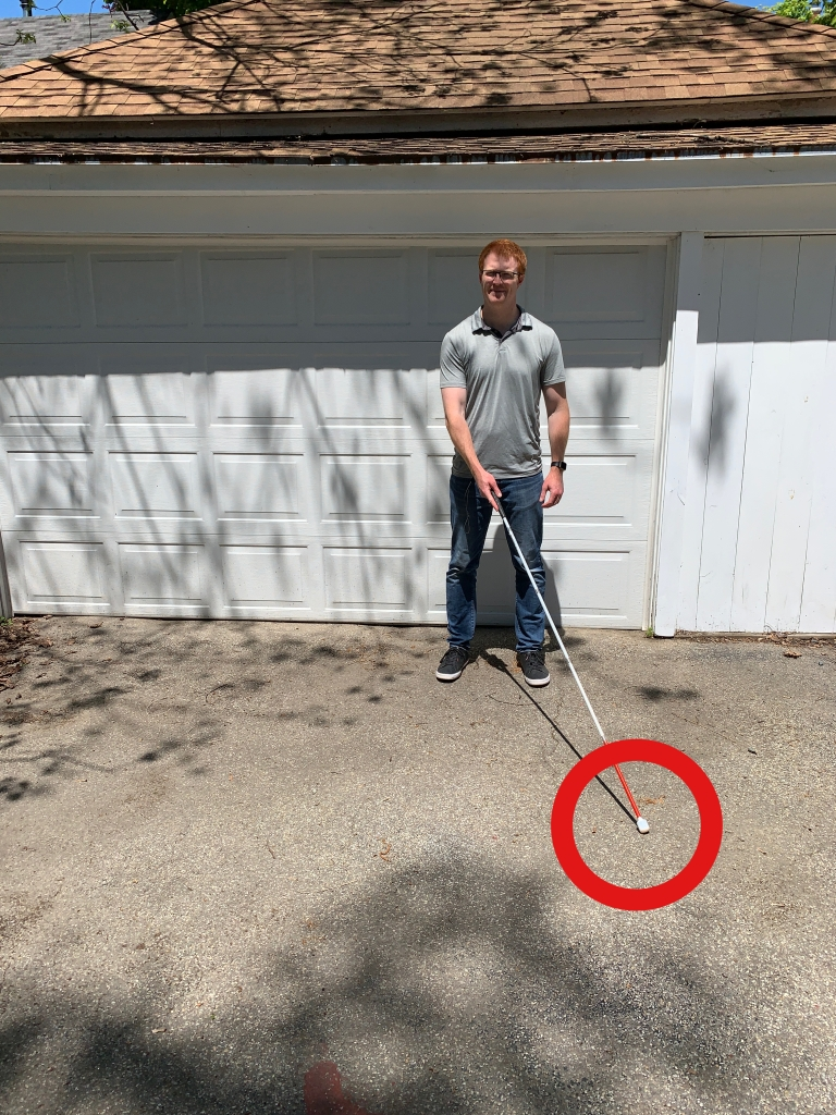 man standing in front of a white garage holding a cane out in front of him with a red arrow around the tip of the cane