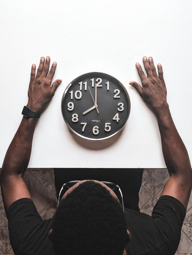 black and white clock sitting on a table with a man looking at it with his hands outstretched around it