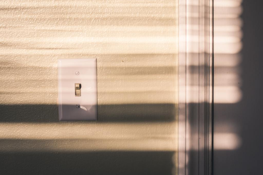 White light switch on a white wall with shadow streaks over it.