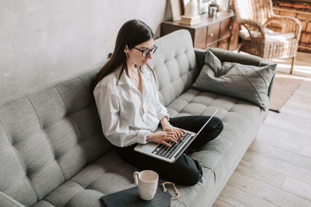 woman sitting on a grey couch working from home on a laptop.