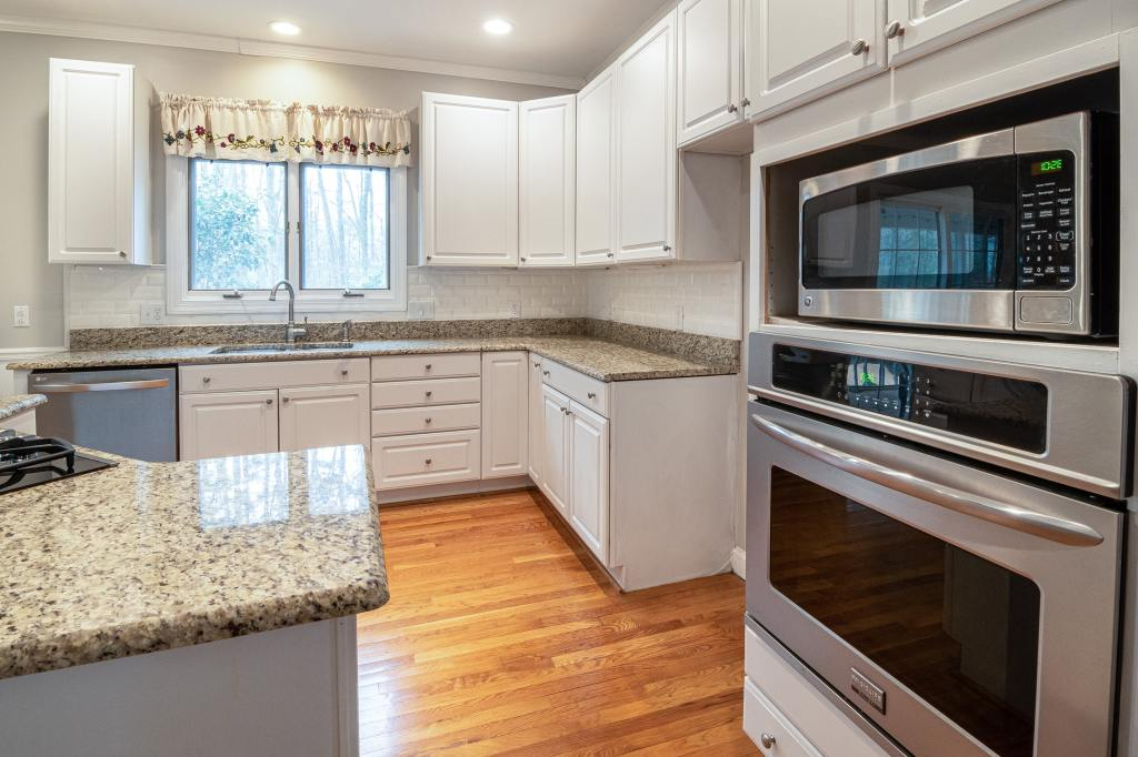 Kitchen with granite counter tops. Microwave sitting on top of an oven embedded in a wall.