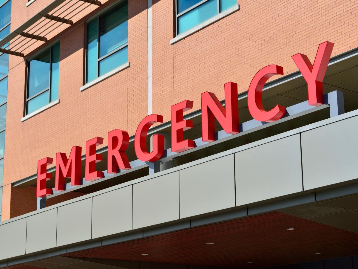 front of a brown hospital building and in red letters says emergency